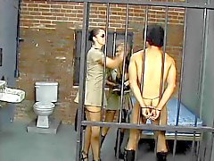 Busty brunette police makes prisoner suck a huge strap on